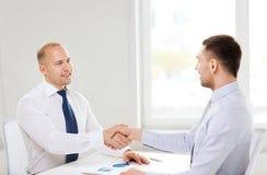 Zwei lächelnde Geschäftsmänner, die Hände im Büro rütteln Stockbild