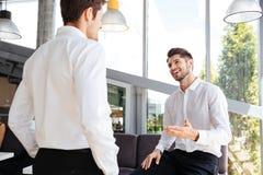 Zwei lächelnde Geschäftsmänner, die im Büro stehen und sprechen Stockbilder