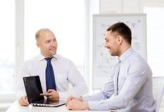 Zwei lächelnde Geschäftsmänner mit Laptop im Büro Stockfotografie