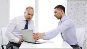 Zwei lächelnde Geschäftsmänner mit Laptop im Büro