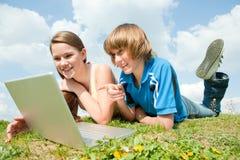 Zwei lächelnde Jugendliche mit Laptop stockfoto