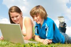 Zwei lächelnde Jugendliche mit Laptop stockfotografie