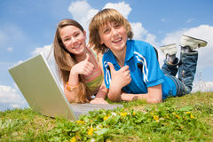 Zwei lächelnde Jugendliche mit Laptop stockbild