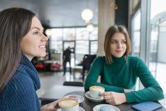 Zwei lächelnde junge Frauen in der Kaffeestube mit Kaffeekunst und Makronen in den Platten, Mädchen, die, Wintersaison trägt warm lizenzfreies stockbild