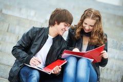 Zwei lächelnde junge Kursteilnehmer, die draußen studieren Stockfoto