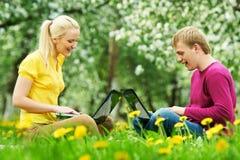 Zwei lächelnde junge Kursteilnehmer draußen mit Computern Stockbild