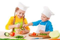 Zwei lächelnde Kinder, die Salat mischen Stockfotografie