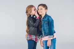 Zwei lächelnde kleine Mädchen, die Geheimnisse flüstern stockfotografie