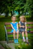 Zwei lächelnde kleine Schwestern sitzen auf Bank Stockbild