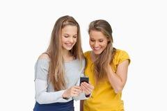 Zwei lächelnde Kursteilnehmer, die einen Mobiltelefonbildschirm schauen Stockfoto