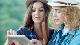 Zwei lächelnde Mädchen des Reisenden, die einen Tabletten-PC in einer Berglandschaft verwenden stock footage