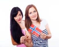 Zwei lächelnde Mädchen, die norwegische Flagge halten. stockfotografie
