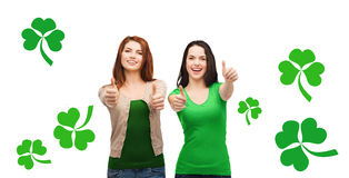 Zwei lächelnde Mädchen, die sich Daumen mit Shamrock zeigen Lizenzfreie Stockfotos