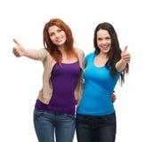 Zwei lächelnde Mädchen, die sich Daumen zeigen Stockfotografie