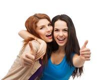 Zwei lächelnde Mädchen, die sich Daumen zeigen Lizenzfreie Stockfotografie