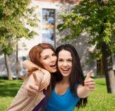 Zwei lächelnde Mädchen, die sich Daumen zeigen Stockbilder