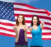 Zwei lächelnde Mädchen, die sich Daumen zeigen Lizenzfreies Stockbild
