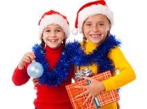 Zwei lächelnde Mädchen mit Weihnachtsdekoration Stockbild