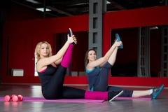 Zwei lächelnde Mädchen tun das Ausdehnen von Übungen auf Matten in Eignungs-CEN Stockfoto