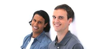 Zwei lächelnde Männer beim Lehnen an einer Wand stock footage