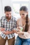 Zwei lächelnde Mitarbeiter beim Aufpassen eines Videos auf dem Mobile in a Lizenzfreie Stockfotos