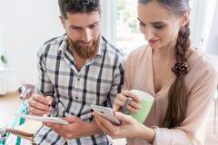 Zwei lächelnde Mitarbeiter beim Aufpassen eines Videos auf dem Mobile in a Stockfoto