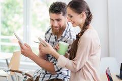 Zwei lächelnde Mitarbeiter beim Aufpassen eines Videos auf dem Mobile Stockfoto