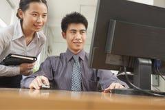 Zwei lächelnde Mitarbeiter, die ein Projekt über dem Bildschirm, im Büro besprechen Stockbild