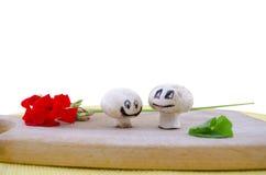 Zwei lächelnde Pilze, die lokalisiert auf Weiß sich verlieben Lizenzfreies Stockbild