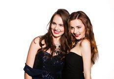 Zwei lächelnde Schönheiten in den Cocktailkleidern Lizenzfreie Stockfotos