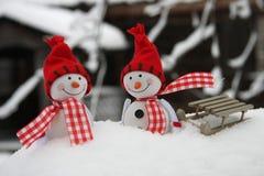 Zwei lächelnde Schneemannfreunde im Schnee Stockbild