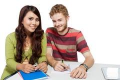 Zwei lächelnde Studenten, die zusammen studieren Stockfotos