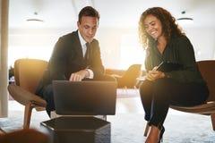 Zwei lächelnde verschiedene Wirtschaftler, die zusammen an einem Laptop arbeiten stockbild