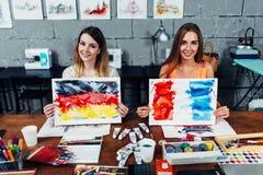 Zwei lächelnde weibliche Illustratoren, die in ihrer Werkstatt hält Papierblätter mit Flaggen von Frankreich und von Deutschland  Lizenzfreies Stockbild