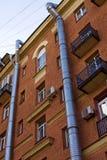 Zwei Lüftungsrohre der Metallluft laufen gelassen entlang die Fassade eines Backsteinbaus stockfotografie