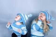 Zwei lachende Mädchen im Schnee Stockfotos