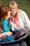 Zwei lachende Schwestern mit Fotoalbum im Park Lizenzfreie Stockbilder