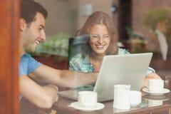 Zwei lachende Studenten, die Laptop betrachten Lizenzfreie Stockbilder