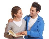 Zwei lachende Studenten mit einem Buch Lizenzfreie Stockfotografie