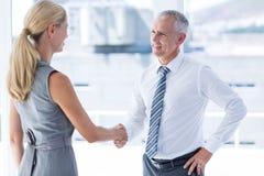 Zwei lächelnde Geschäftsleute, die Hände rütteln Stockbild