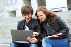Zwei lächelnde junge Kursteilnehmer draußen Lizenzfreie Stockbilder