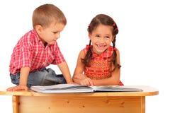 Zwei lächelnde Kinder, die das Buch auf dem Schreibtisch lesen Stockfotos