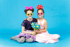 Zwei lächelnde Mädchen in der lustigen Sonnenbrille, die auf blauem Hintergrund sitzt Stockfotos