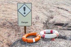 Zwei Lebenbojen, die auf dem Felsen mit Warnschild orange und weiß sind, sind Stockfoto