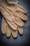 Zwei lederne Schutzhandschuhe auf dunklem Holz Stockbild
