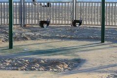 Zwei leere Baby-Schwingen-Sitze in Sandy Park Stockbilder