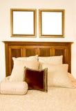 Zwei leere Bilderrahmen über Bett Stockbild