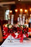 Zwei leere Heiratsgläser, verziert mit dem Grün, den roten Rosen und dem Band, stehend auf dem Bankettisch Lizenzfreie Stockfotos