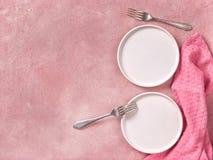 Zwei leere Nachtischteller, Gabeln und Serviette auf rosa konkretem Hintergrund lizenzfreie stockfotografie