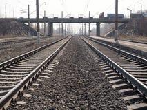 Zwei leere parallele Bahnlinien, Schienen, Lagerschwellen, Schuttabschluß oben, Weitwinkel-, getontes Braun, selektiver Fokus stockfotografie